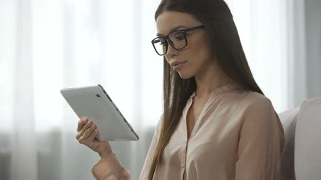 inbox : Elegant lady in glasses analysing email letters, checking inbox folder on tablet