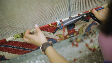 dywan : Female weaving carpet, cutting woven threads with scissors, traditional craft
