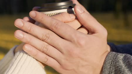 attitude : Cup of coffee in lovers hands outdoors, keeping heat of love, tenderness