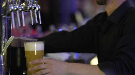 frothy : Bar employee hands customer a big glass of fresh beer with frothy white foam