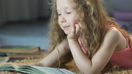 bonitinho : Cute curly girl lying on carpet and reading fairy tales aloud, happy childhood Stock Footage