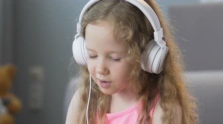 görgetés : Nice curly-haired girl listening to music in headphones and singing songs