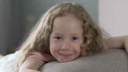 při pohledu na fotoaparát : Cheerful curly haired girl lying on sofa and smiling into camera, happiness Dostupné videozáznamy