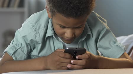 schoolkid : Boy holding mobile phone and playing game, child addiction to gadgets, engrossed
