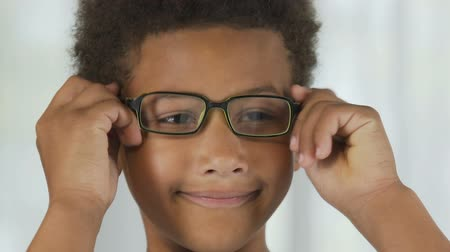 gururlu : Small boy putting on glasses in front of mirror, satisfied, eyesight correction Stok Video