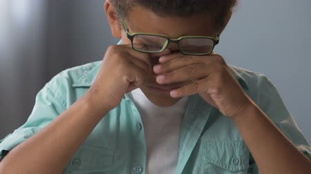 multinational : Little biracial boy in glasses doing homework, rubbing eyes, strained eyesight