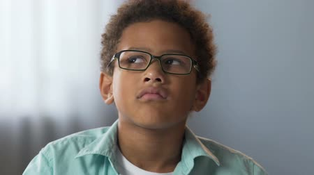 mateřská škola : Mixed-race male kid in glasses thinking carefully, thoughtful face expression