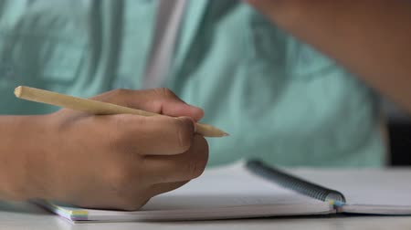 estudioso : Schoolboy doing home assignment, learning how to write, calligraphy practice Stock Footage