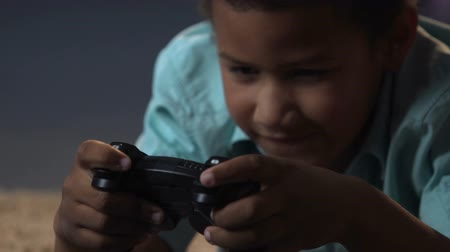 addiktív : Mixed-race boy lying on floor with play station control and playing video games Stock mozgókép