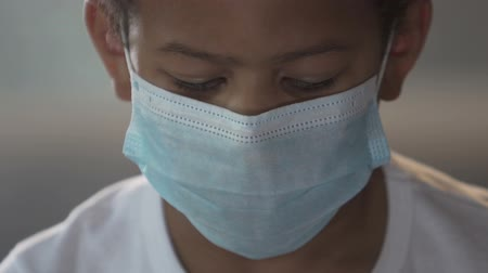 dispanser : Biracial child in face mask looking at camera angrily, medical dispensary Stok Video
