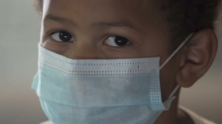 dispensary : African boy wearing medical mask and looking at camera, infection, healthcare