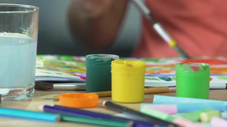 plněné : Table filled with acrylic paint and brushes, children drawing in background Dostupné videozáznamy