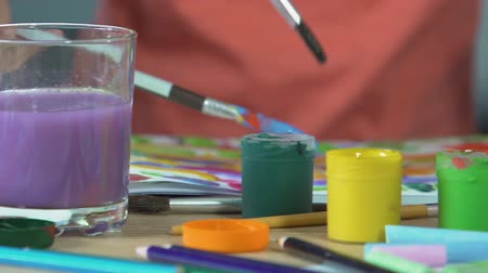 clearing the table : Tiny girls hand washing painting brush in colorful water, creative fun time