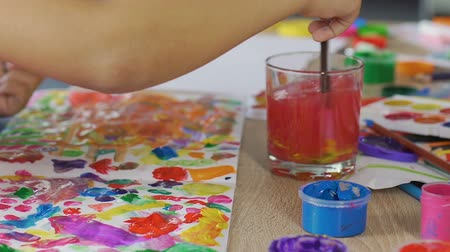 clearing the table : Small kid blends all possible colors on a piece of paper, imaginative mind
