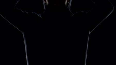 bandido : Young man in black hoodie invisible in night darkness, secret gangster closeup