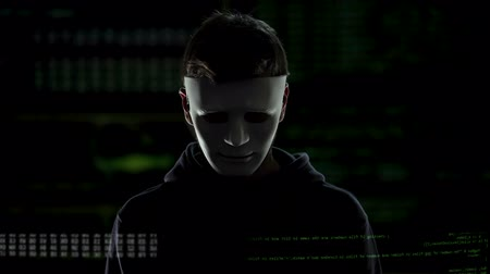 vulnerability : Dangerous man in white mask on codes and numbers background, hacking concept Stock Footage