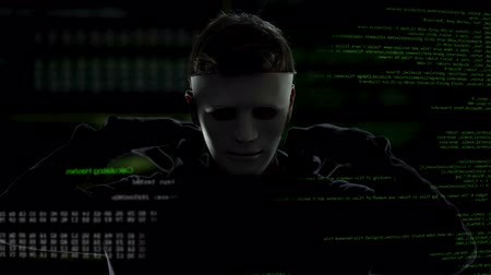 vulnerability : Scary hacker in mask putting on his black hood, cyber terrorism and hacking Stock Footage