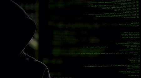 vulnerability : Faceless dark man on codes background stealing personal data, launching malware Stock Footage