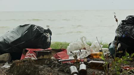 rothadó : Empty bottles and containers polluting seashore, tons of garbage damaging nature