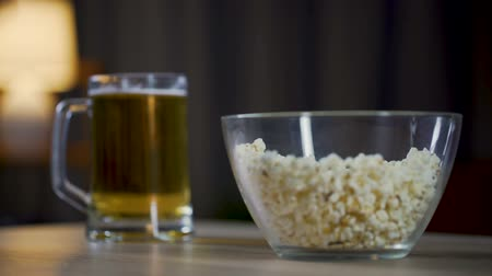 unhealthy eating : Mans hand taking popcorn from the bowl, male drinking beer and watching movie
