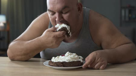 cukorbaj : Obese person eating cake with whipped cream greedily and quickly, addiction
