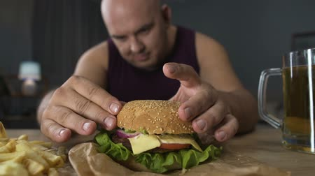 high calories : Overeating, obese man cooking big burger, gourmet admiring his meal, close-up Stock Footage
