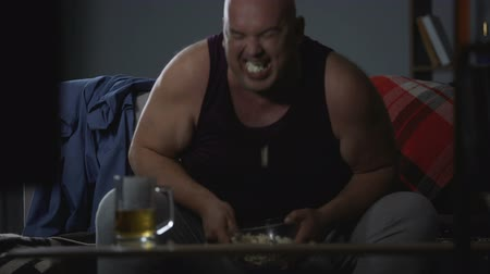 круглолицый : Man watching TV with popcorn and beer, messy careless lifestyle, food addiction
