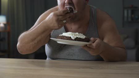 motivo : Adult overweight man gobbling cake and licking his fingers, diabetes, junk food