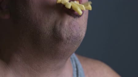 incapacidade : Fast food addict eating french fries, inability to resist unhealthy foodstuff