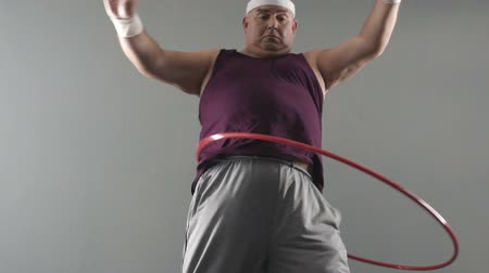 целлюлит : Obese male trying to twist hula hoop, dreams of healthy and fit body, weightloss