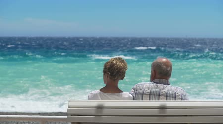 stroll : Aged couple sitting next to each other on bench by waterfront, facing choppy sea