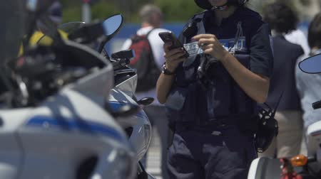 patrolman : Female police officer standing next to motorbike, checking mobile phone on duty Stock Footage