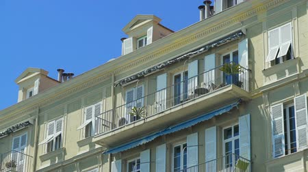 markiza : Focus on open balcony on top floor of building with awning swayed by strong wind