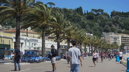 enjoyable : People walking down busy pedestrian way on windy day, palms rowing up alongside