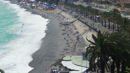 elválasztott : People sunbathing on pebble beach by ocean, active traffic on road, resort city