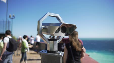 izlenim : Binoculars at observation deck on sunny day, people moving around at background