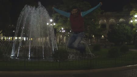 enjoyable : Happy young man jumping up, fountain and night streetlights at back, slow-mo Stock Footage