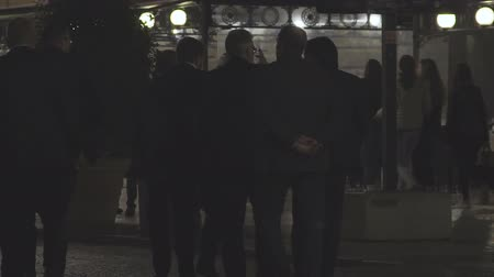 compromise : Group of business men in suits walking down dark street, back view, slow motion
