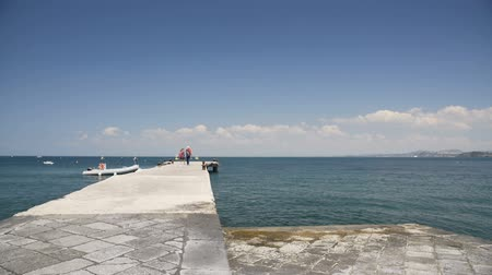 vízpart : Female and male tourists walking on pier and enjoying beautiful seascape