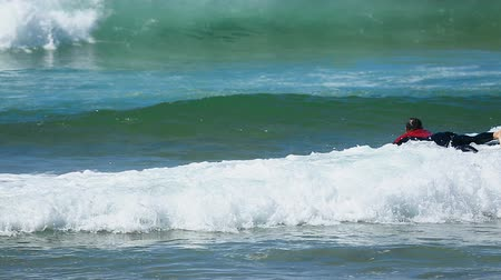 dinlenmek : Ocean wave taking young male on surfing board back closer to seashore, sport