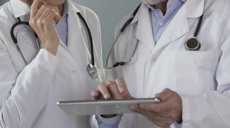 discharging : Doctors checking electronic medical records on tablet, working on diagnosis Stock Footage
