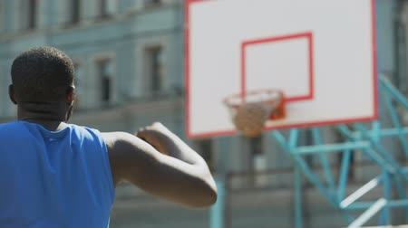 top sürme : Professional basketball player throwing ball into basket, active training Stok Video