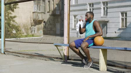 streetball : Strong basketball player sitting on bench and drinking mineral water, sport