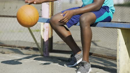 bank : Close-up of African American male sitting on the bench and playing ball, sadness