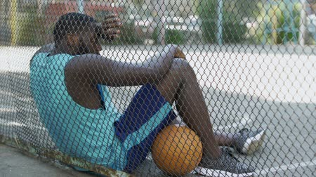 esportivo : Tired African-American basketball player relaxing after game at stadium, hobby