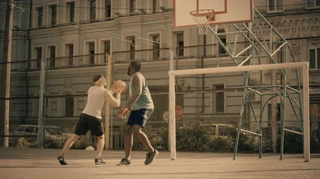 top sürme : White and black men playing basketball, active friends having fun, good memories Stok Video