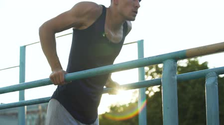 bodyweight : Purposeful young male doing exercises on parallel crossbars outdoors, sport