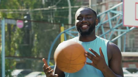 top sürme : Happy man throwing ball from one hand to another, proud of streetball victory
