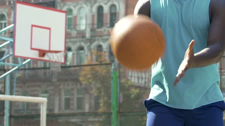 elmélet : Trainer playing basketball outdoors, taking and passing ball, teamwork in sport