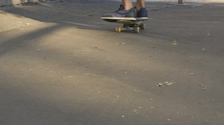 cultura juvenil : Male teenager learning to keep balance, riding skateboard, outdoor activities